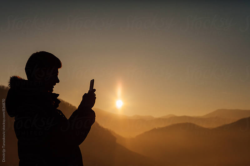 Man with mobile phone taking photos of the sunset in  the mountains by Dimitrije Tanaskovic for Stocksy United