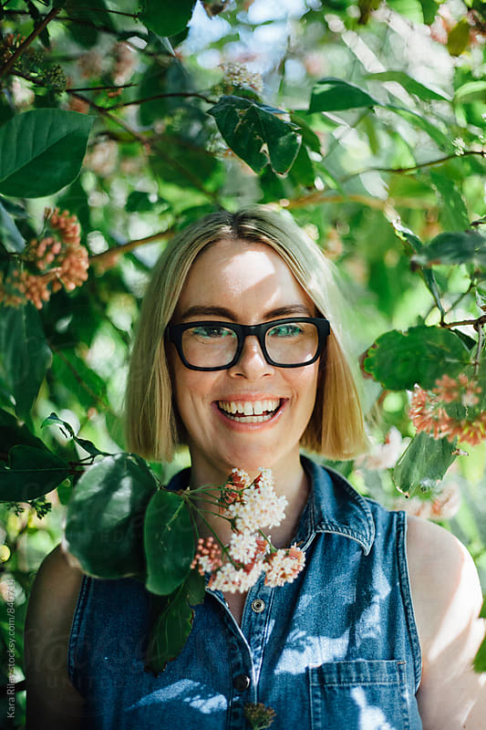 Blonde Woman with glasses amongst flowers by Kara Riley for Stocksy United