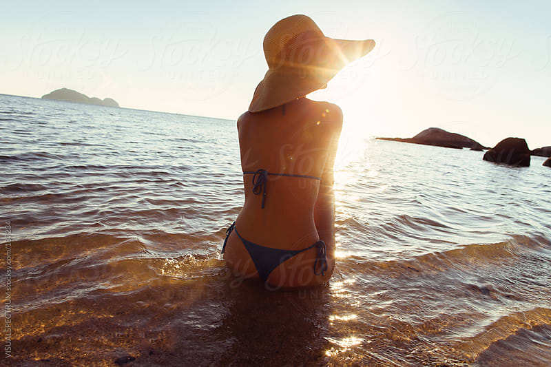 Beautiful Woman Watching Sunset on Beach by VISUALSPECTRUM for Stocksy United