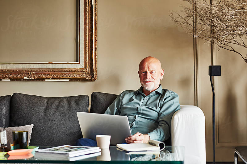 Confident Senior Businessman With Laptop On Sofa by ALTO IMAGES for Stocksy United