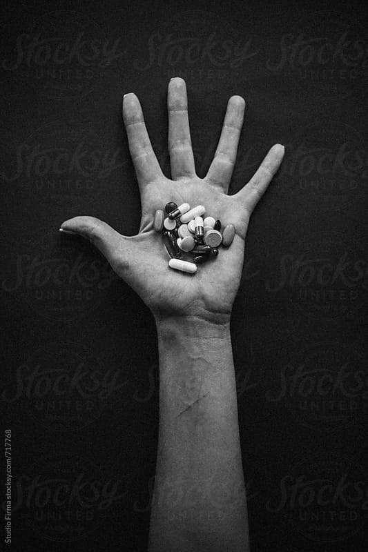 Hand of a young Woman holding a pills. by Studio Firma for Stocksy United