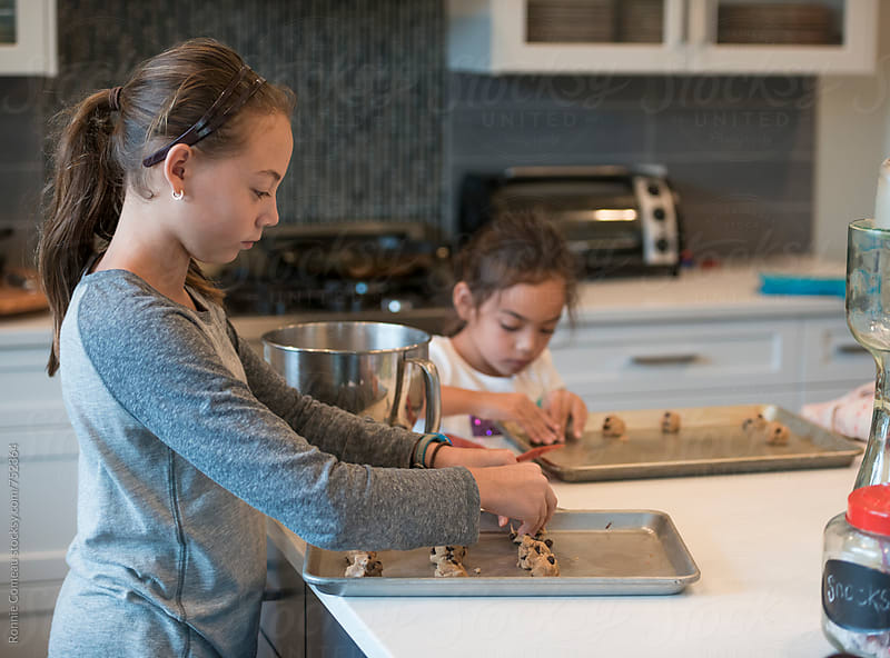 Sisters Baking Chocolate Chip Cookies by Ronnie Comeau for Stocksy United
