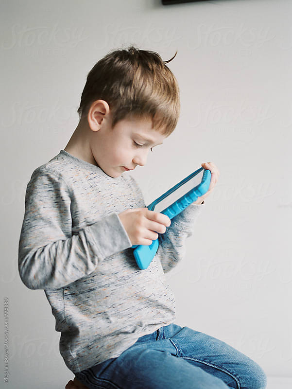 Boy kneeling playing electronic device with ripped jeans by Meghan Boyer for Stocksy United