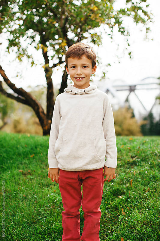 Portrait of an adorable little boy standing in the park. by BONNINSTUDIO for Stocksy United
