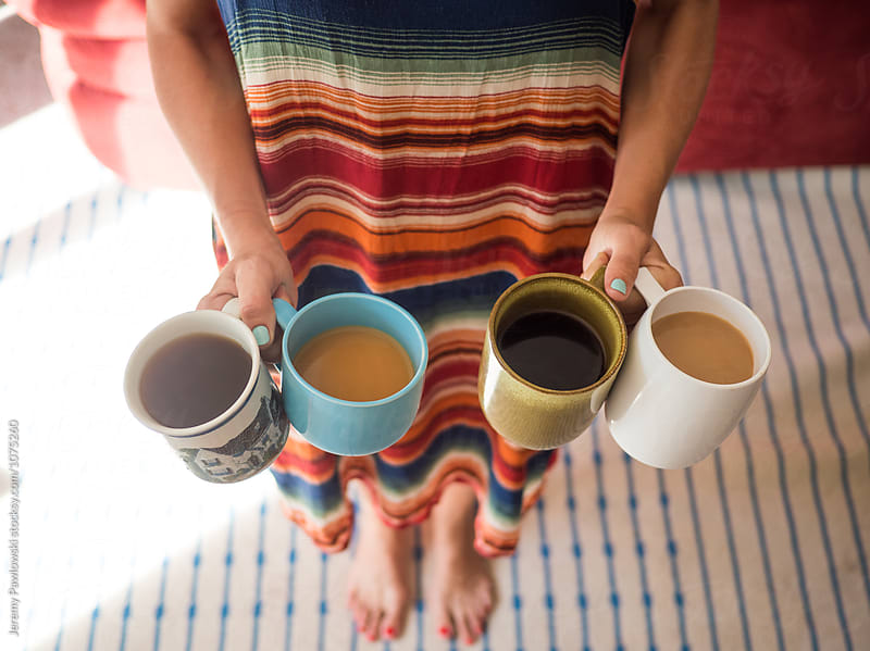 Young woman in dress holding four eccentric mugs full of coffee in a home by Jeremy Pawlowski for Stocksy United