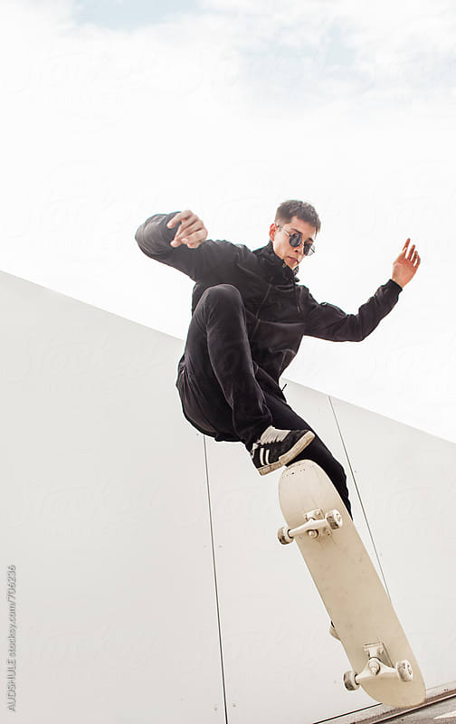 Skateboarder doing trick. by Marko Milanovic for Stocksy United