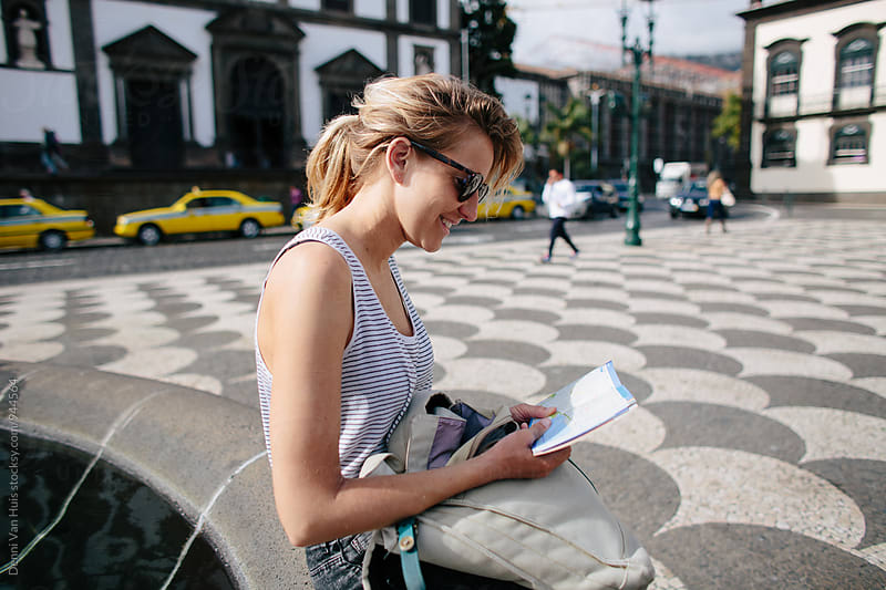 Woman reading a map to explore a city by Denni Van Huis for Stocksy United