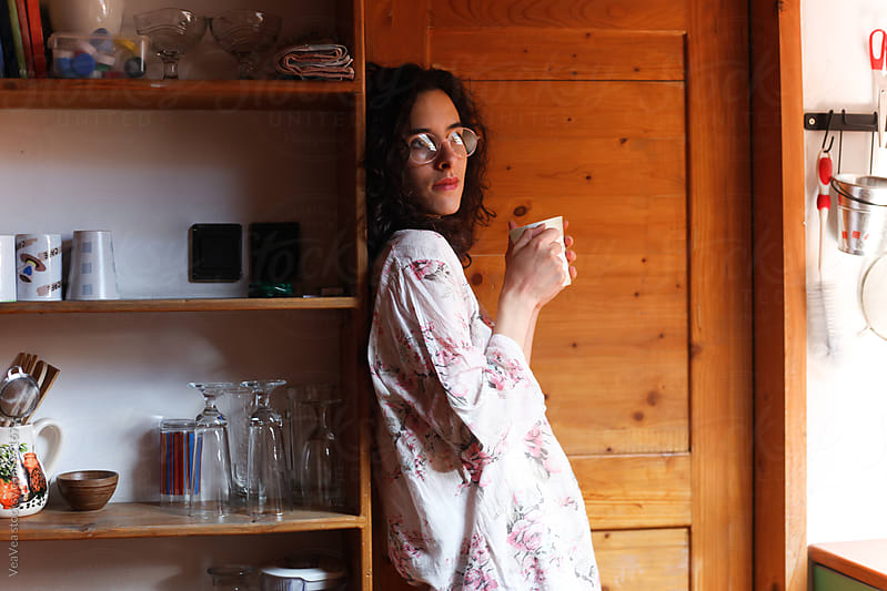 Young woman drinking coffee in the kitchen  by Marija Mandic for Stocksy United