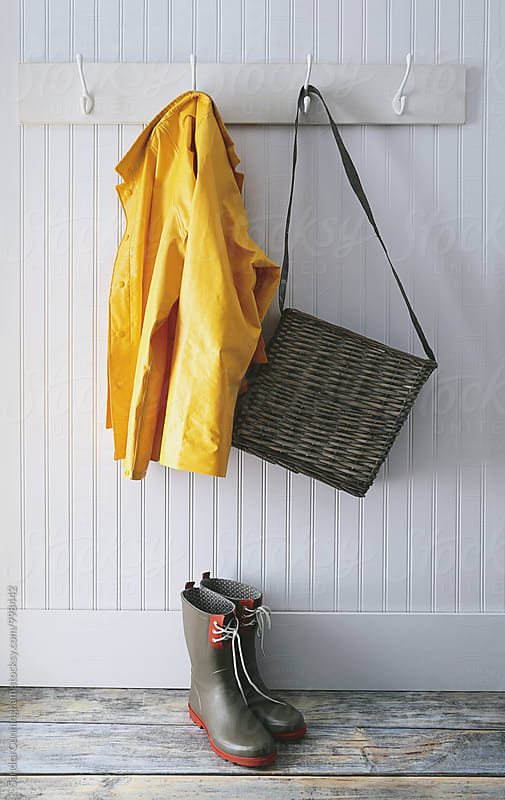 Raincoat and wicker basket hanging by Sandra Cunningham for Stocksy United