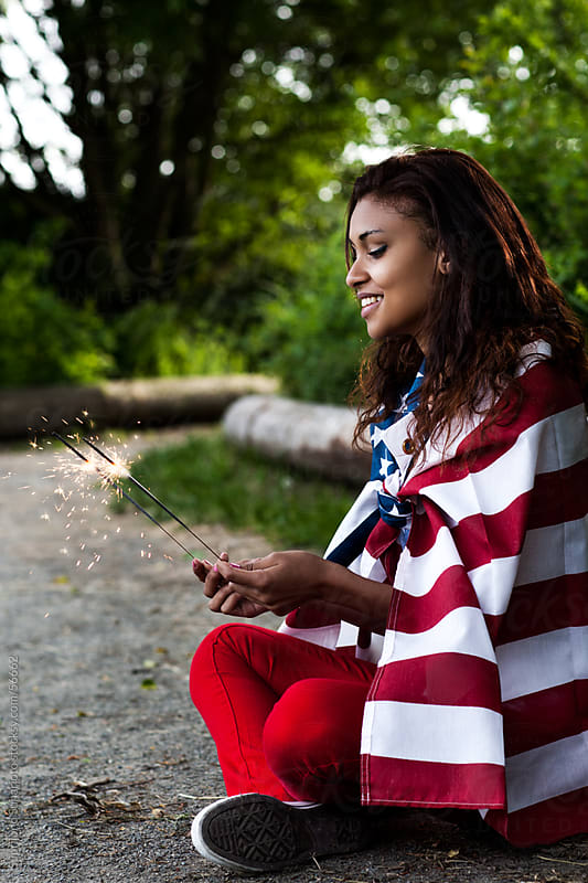 Beautiful young African American woman holding an American flag  by Suprijono Suharjoto for Stocksy United