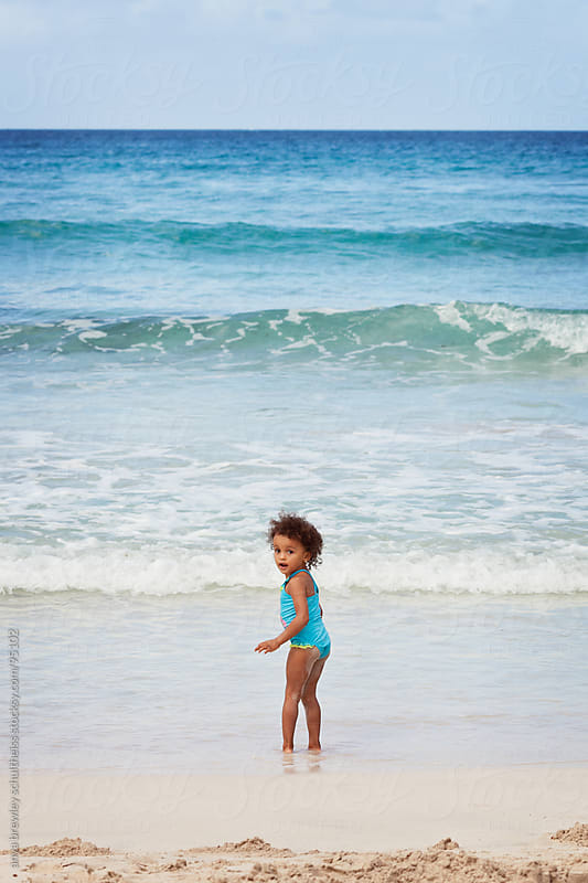 Little girl on a beach watching blue waves by anya brewley schultheiss for Stocksy United