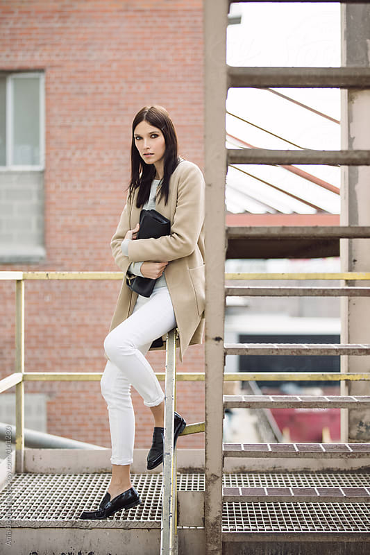 A woman casually dressed sitting on a metal staircase holding a clutch by Ania Boniecka for Stocksy United