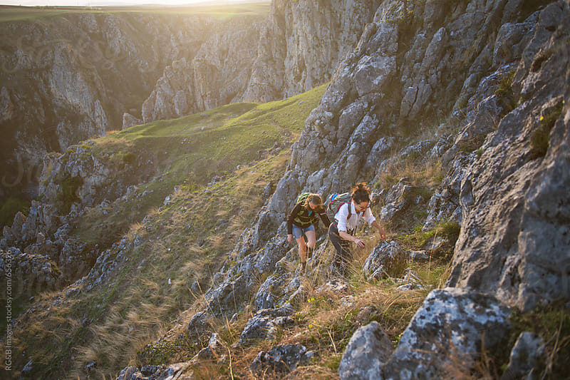 Young female hikers climbing a rocky hill by RG&B Images for Stocksy United