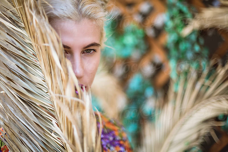 blond girl hiding behind dry palm frond by Image Supply Co for Stocksy United