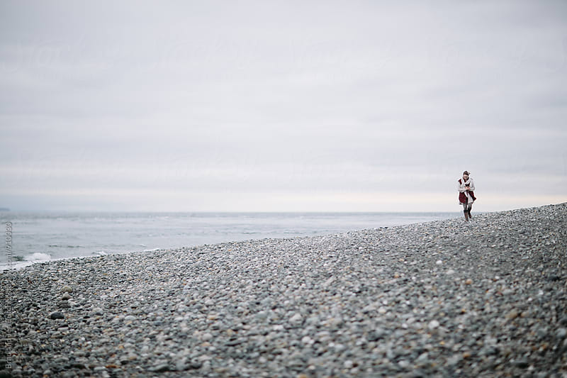 Woman walking beach in winter by Brad and Jen Butcher for Stocksy United