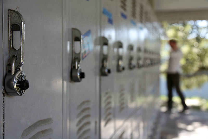 Lockers at a school with a student by Carolyn Lagattuta for Stocksy United