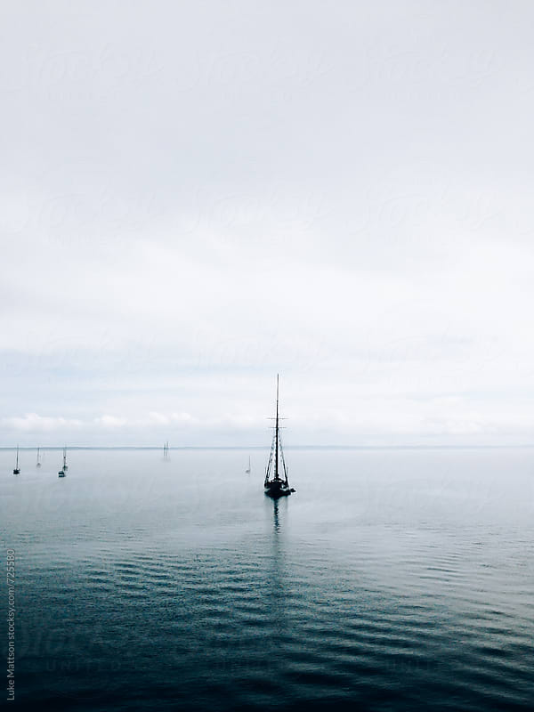 Sailboat Anchored In Still Ocean Waters by Luke Mattson for Stocksy United