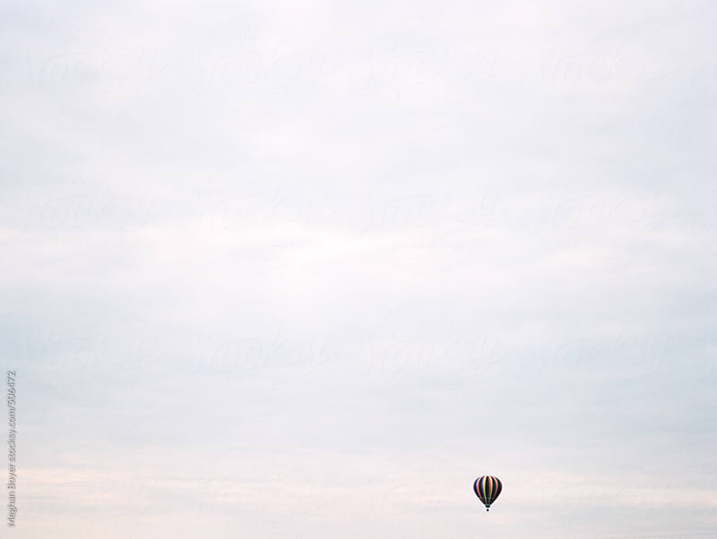 a tiny hot air balloon in a big pastel sky by Meghan Boyer for Stocksy United