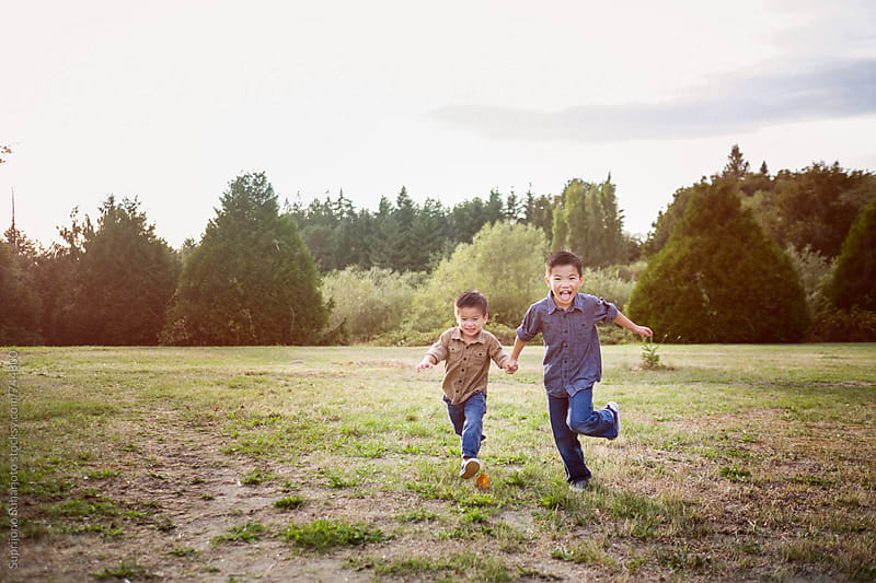 Portrait of Asian kids running outdoor by Suprijono Suharjoto for Stocksy United