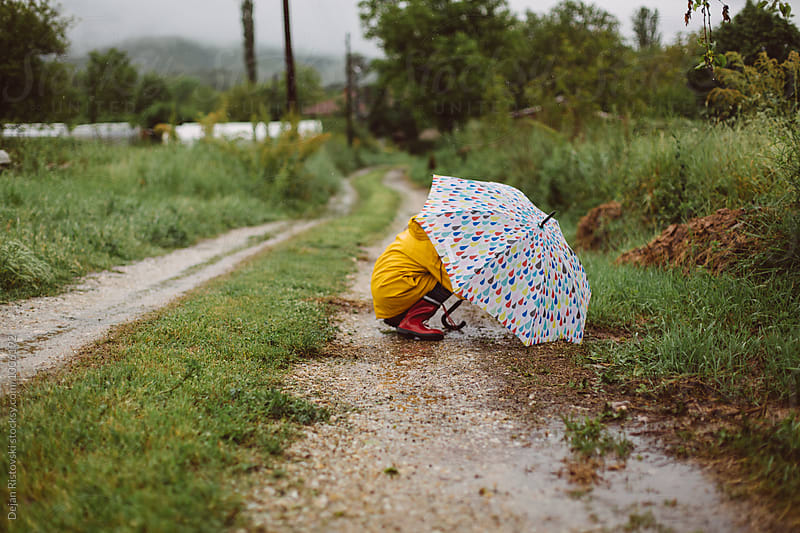 Girl playing under umbrella. by Dejan Ristovski for Stocksy United