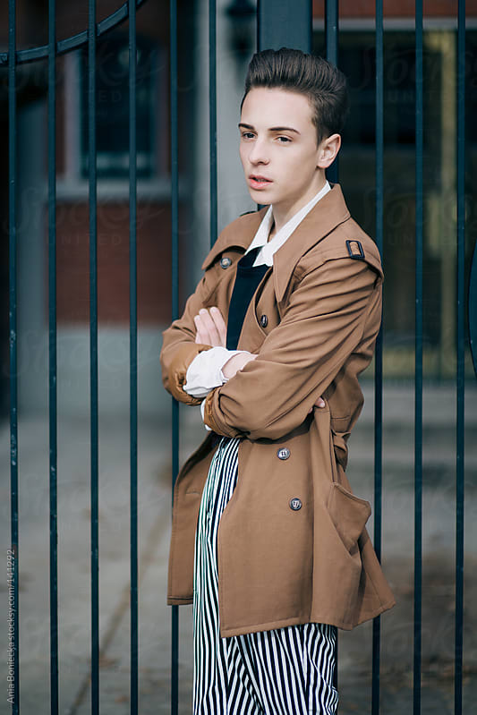 A well dressed man standing against a metal gate looking into the distance by Ania Boniecka for Stocksy United