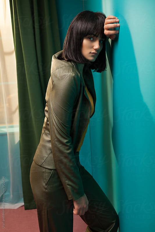 young brunette leaning on a wall in a room by Ulaş and Merve for Stocksy United