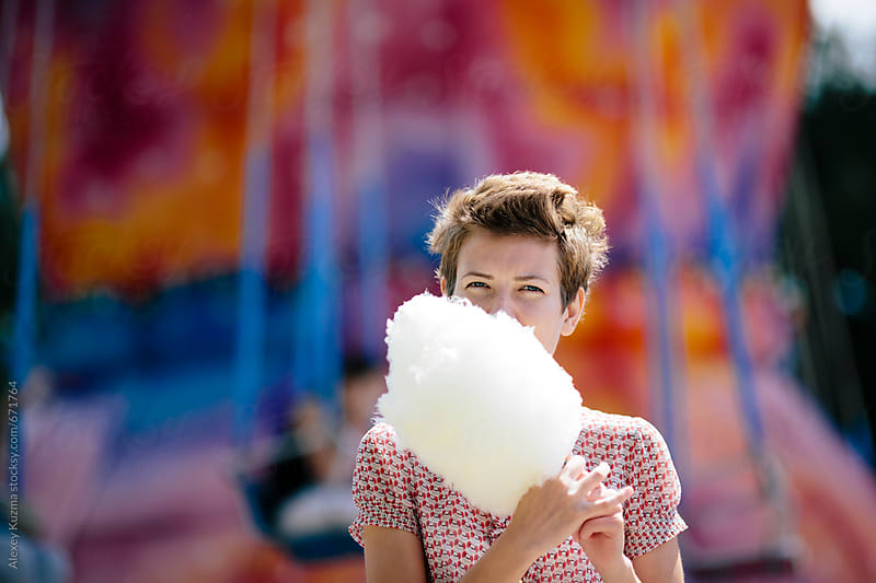 happy young woman eating cotton candy. by Alexey Kuzma for Stocksy United