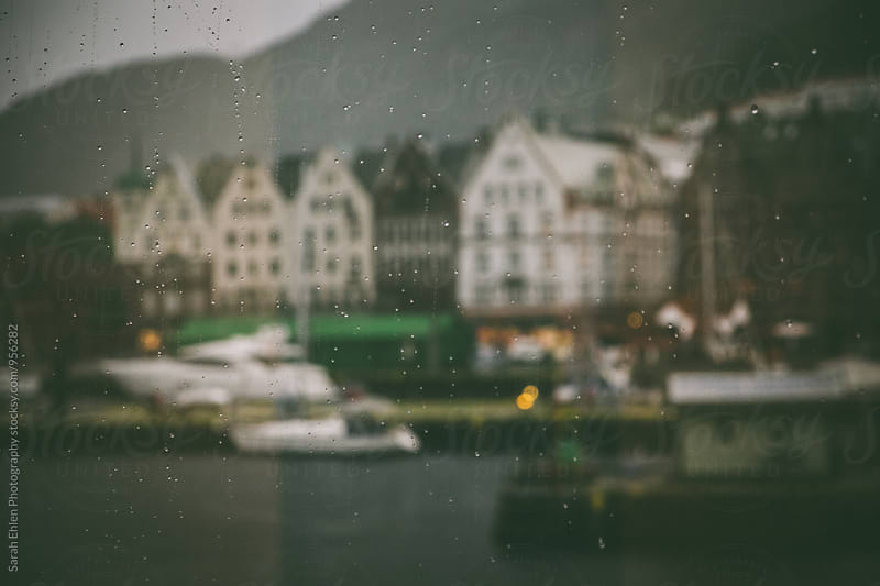 Blurry view of boats through raindrops on a window overlooking a harbor by Sarah Ehlen Photography for Stocksy United