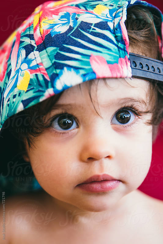Stylish baby wearing a colourful flower cap by Inuk Studio for Stocksy United