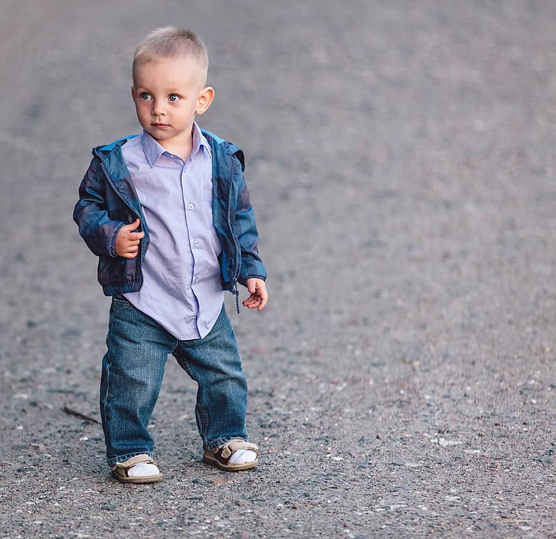 Baby boy standing outdorrs portrait by Ilya for Stocksy United