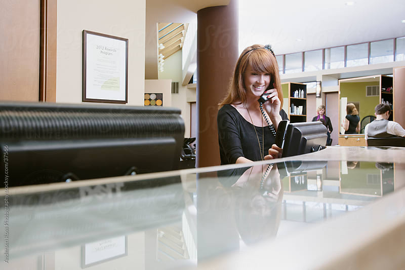 Woman talking on phone at reception desk by Andersen Ross Photography for Stocksy United