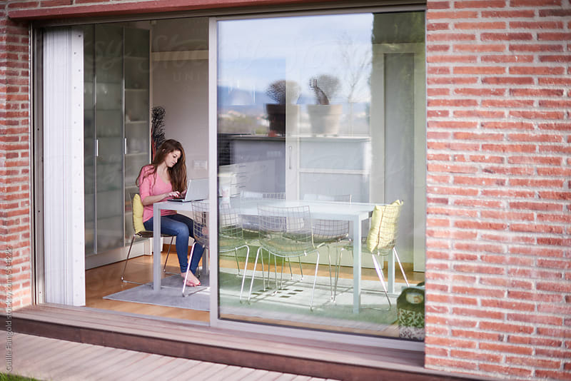 view from outdoors: woman using her laptop inside her house by Guille Faingold for Stocksy United