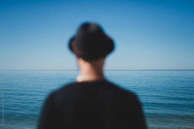 Man looking at sea by Lauren Naefe for Stocksy United