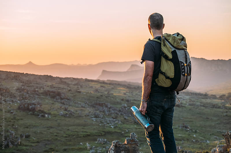Hiker with backpack and thermos overlooking a mountainous sunset view by Micky Wiswedel for Stocksy United