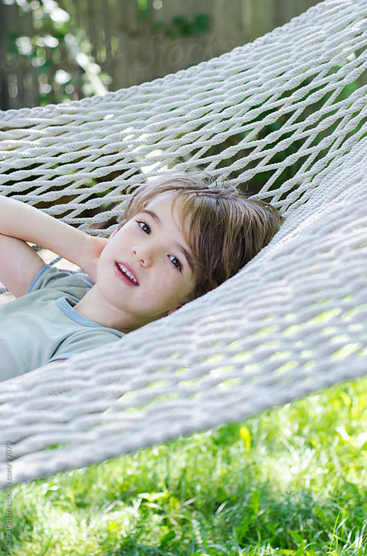 Boy relaxes on backyard hammock in summertime by Cara Dolan for Stocksy United