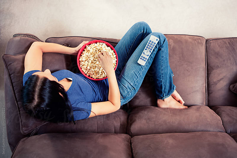 Television: Woman Relaxes on Couch Watching TV by Sean Locke for Stocksy United