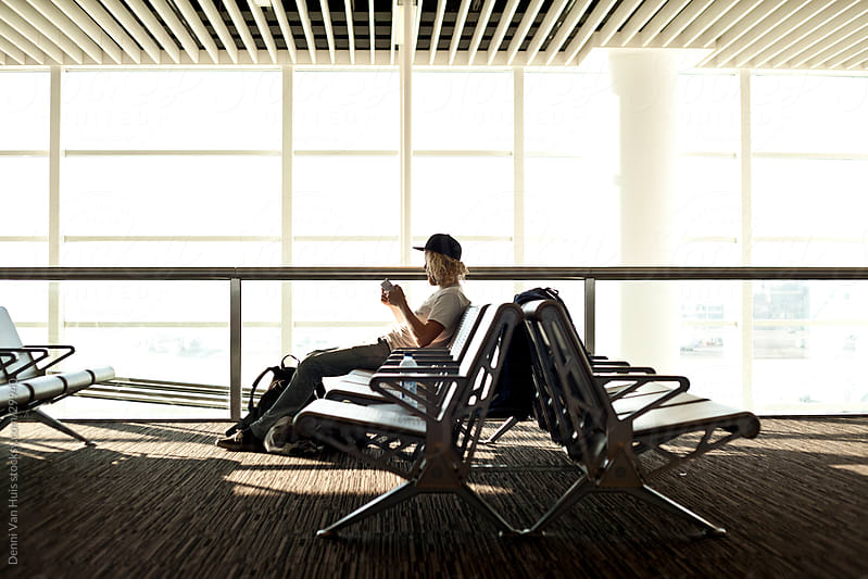Young man reading while waiting on a airport for his flight to leave by Denni Van Huis for Stocksy United
