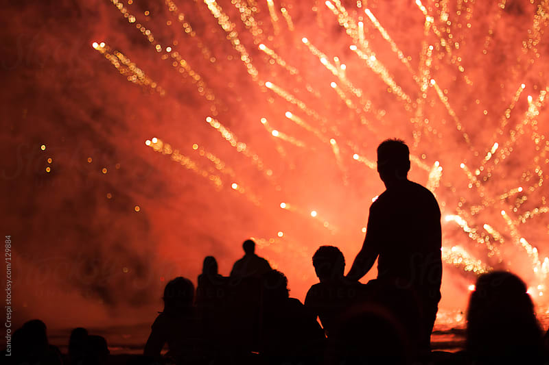 Group of people enjoying fireworks show by Leandro Crespi for Stocksy United