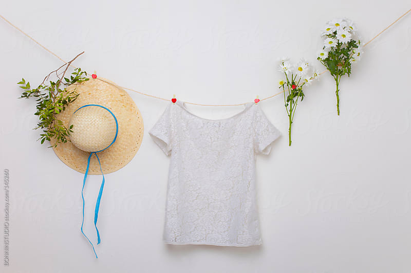 Still life of white shirt, two bouquets of daisies and straw hat hanging. by BONNINSTUDIO for Stocksy United