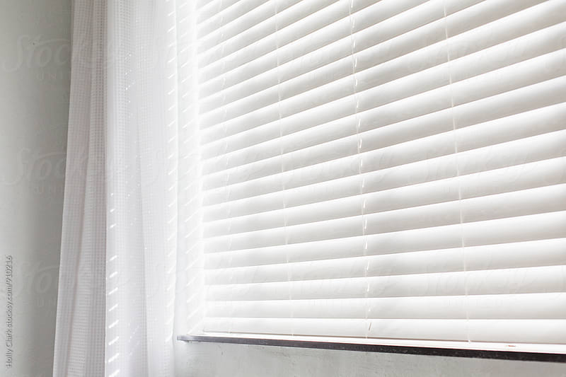 White blinds block out a sunny day by Holly Clark for Stocksy United