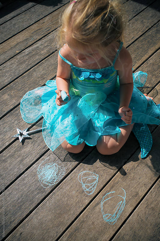 Little girl writing with chalk on deck by Rowena Naylor for Stocksy United