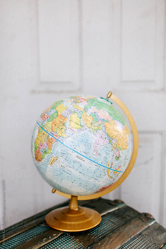 A world globe sitting on an antique storage chest.  by Kristen Curette Hines for Stocksy United