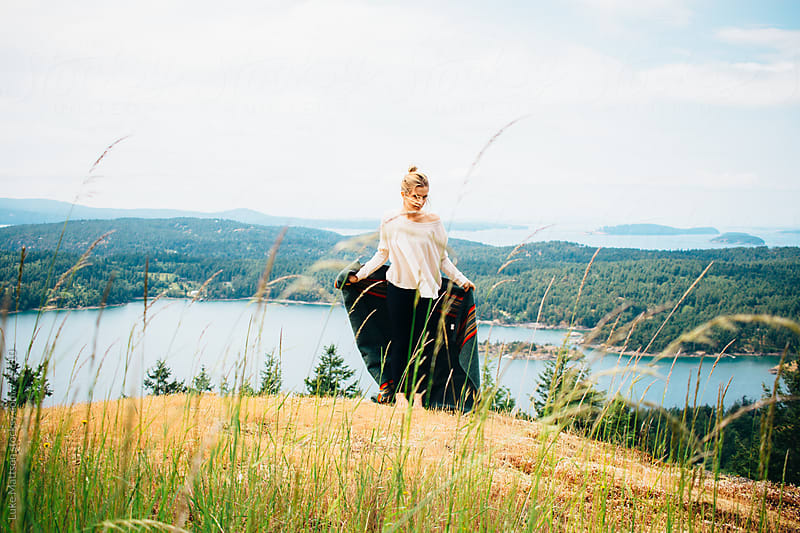 Young Blonde Woman Holding Wool Blanket Standing On Forest Island Hillside by Luke Mattson for Stocksy United