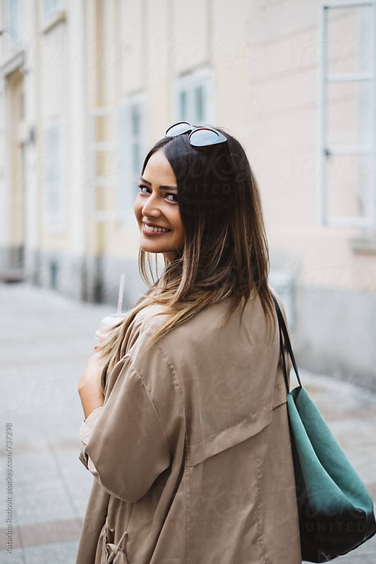 Beautiful Brunette Woman Walking Down the Street  by Katarina Radovic for Stocksy United
