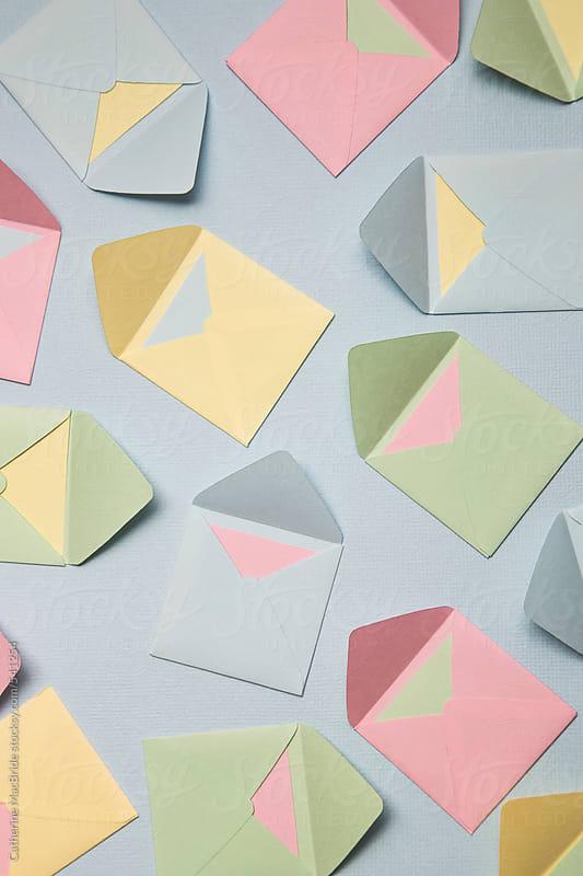Pastel coloured envelopes on Blue Background by Catherine MacBride for Stocksy United
