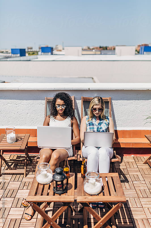 Two Women on a Rooftop Using their Laptops in a Summer Day by VICTOR TORRES for Stocksy United