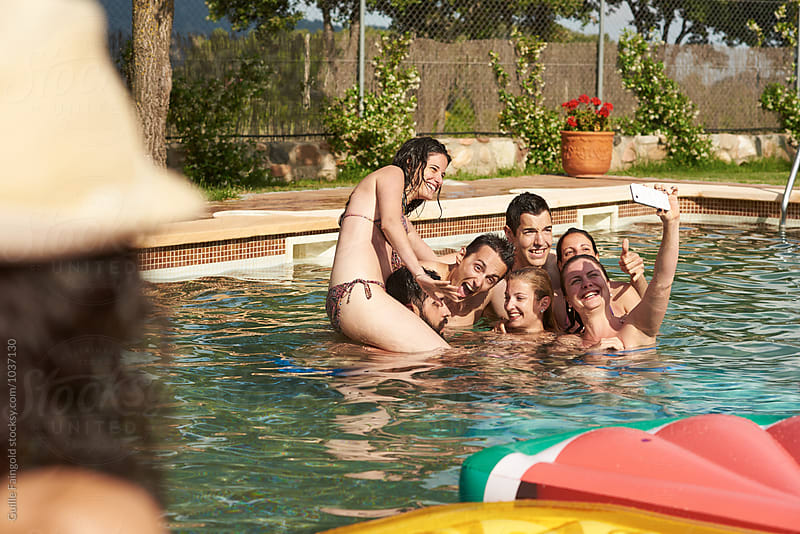 Group of friends making selfie in pool by Guille Faingold for Stocksy United