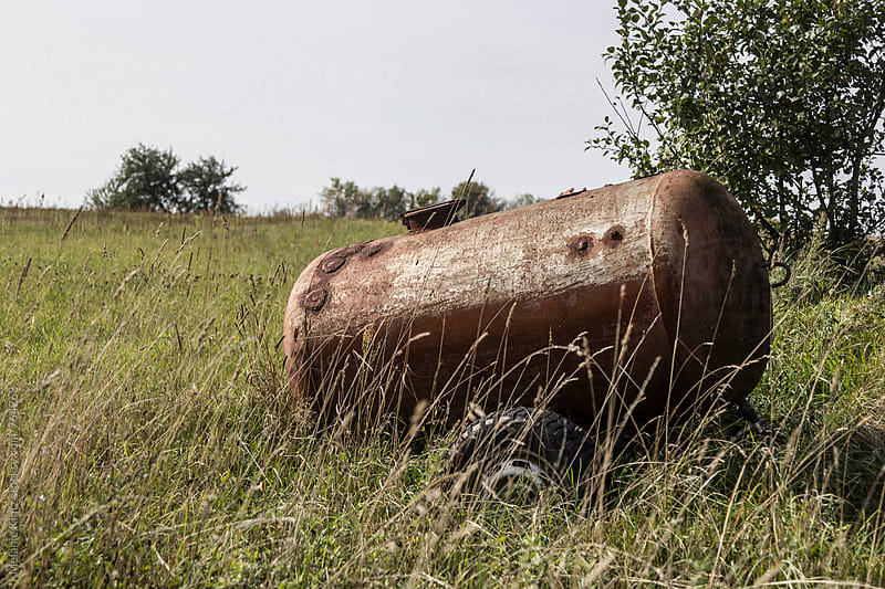 Old rusty water tank on a meadow by Melanie Kintz for Stocksy United