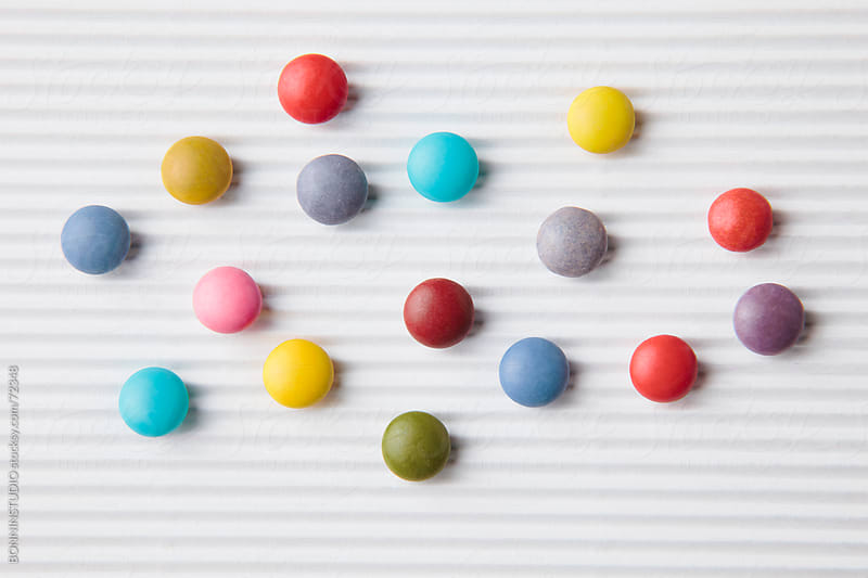 Close up of  colorful chocolate coated candy on white background. by BONNINSTUDIO for Stocksy United
