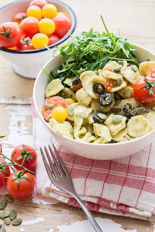 Arugul and pasta salad with cherry tomatoes and black olives with pesto and pumpkin seeds by Marta Muñoz-Calero Calderon for Stocksy United